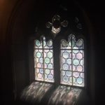Image depicts stained-glass window inside the John Rylands Library